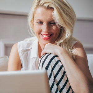 Smiling Woman Surfing the Net at Home