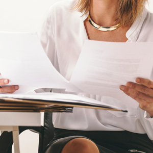 Close up of business woman reading a documents at office.